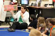 Teacher reading a picture book to children