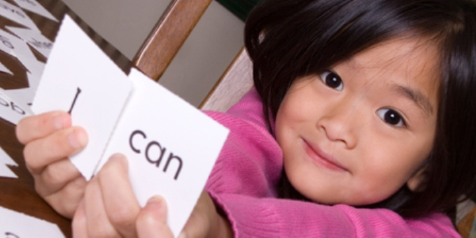"Special Education Student holding cards that read ""I can"""