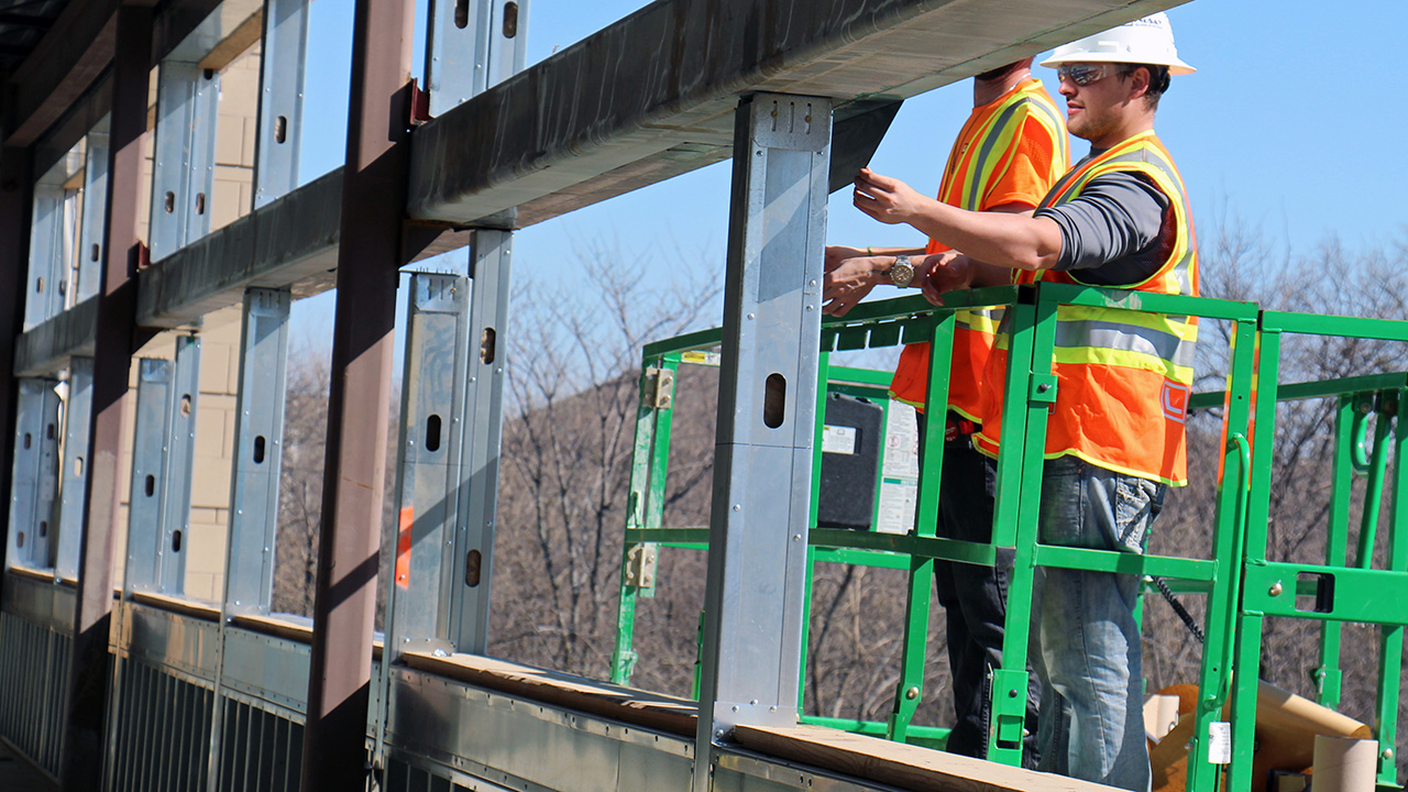 Construction workers adjust the framing on an elementary school window